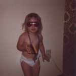 Jessica holds her big sister's Owl calculator, wearing tons of bead necklaces and big sunglasses in this classic diaper-clad photo. (8/1979)