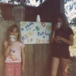 Jessica and Kathleen sell Kool-Aid at a homemade stand in the back yard. (6/1982)