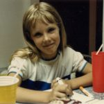 Jessica shrugging at the camera while drawing with markers. (6/1985)