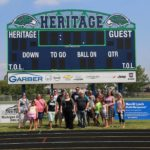 Jessica poses with classmates in front of the Heritage High School scoreboard during a tour for their 20th reunion. (7/25/015)